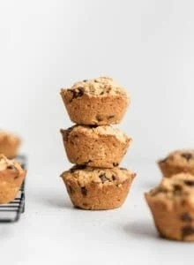A stack of 3 small muffins on a counter beside a cooling rack.