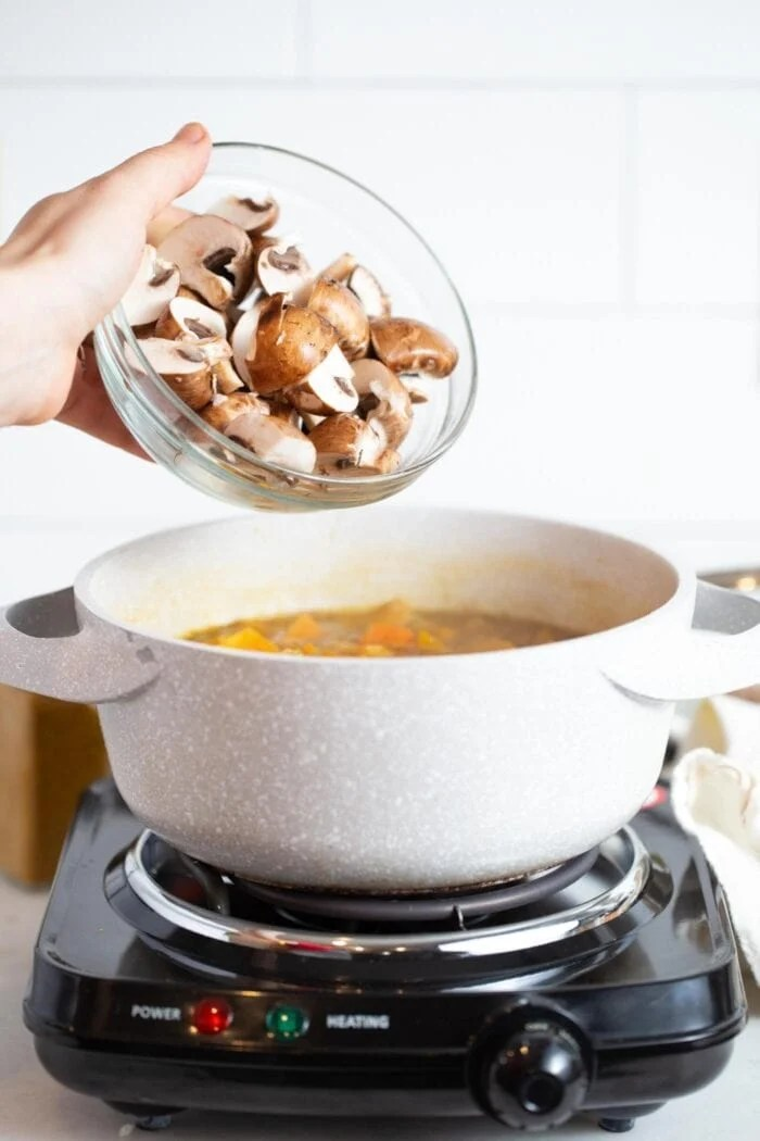 Adding chopped mushrooms to a large bowl of stew.