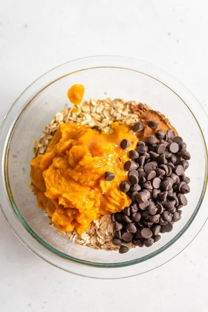 Pumpkin, oats, chocolate chips and cinnamon in a glass mixing bowl.