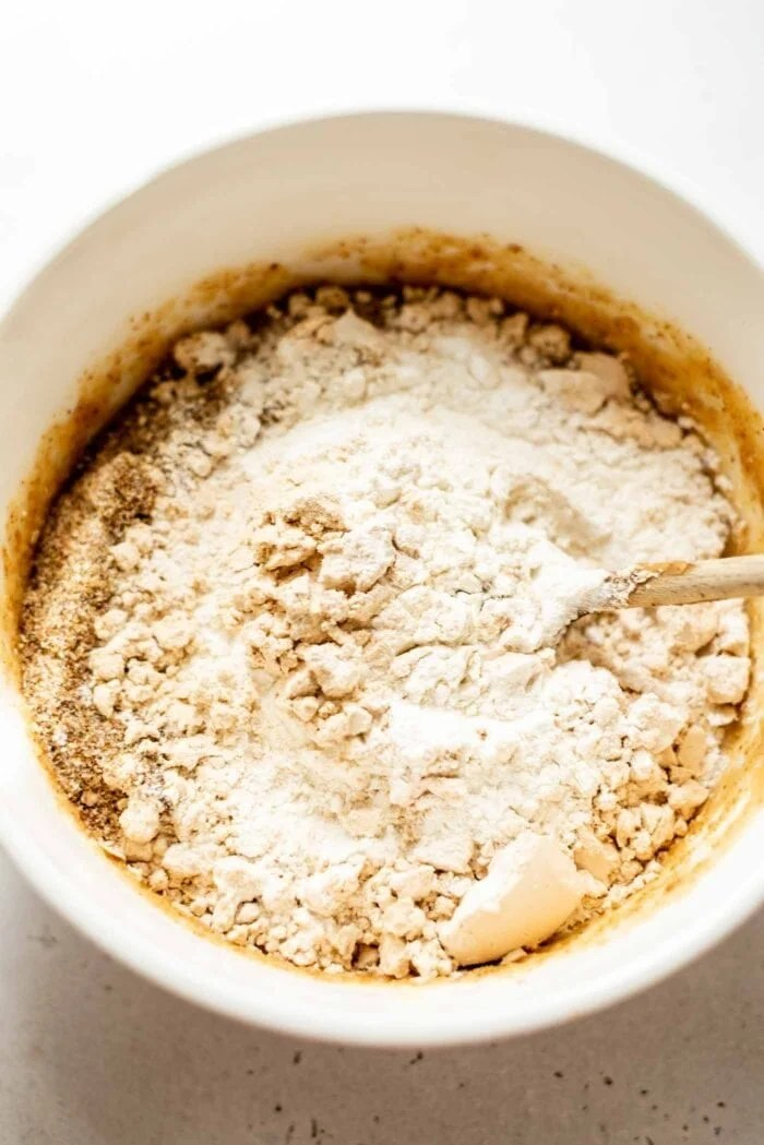 Dry baking ingredients being mixed into wet ingredients in a mixing bowl.