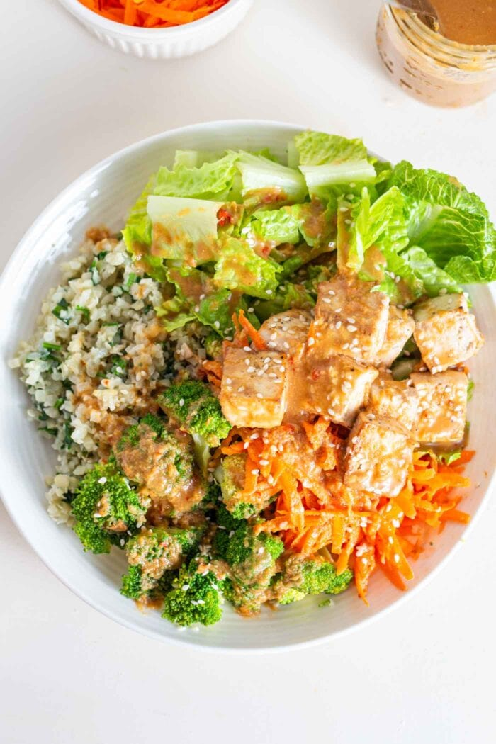 A overhead image of a bowl with carrot, tofu, broccoli, cauliflower rice, tofu and peanut sauce.