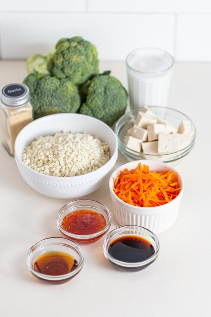 Broccoli, cauliflower rice, carrot, tofu and sauce in containers on a counter.