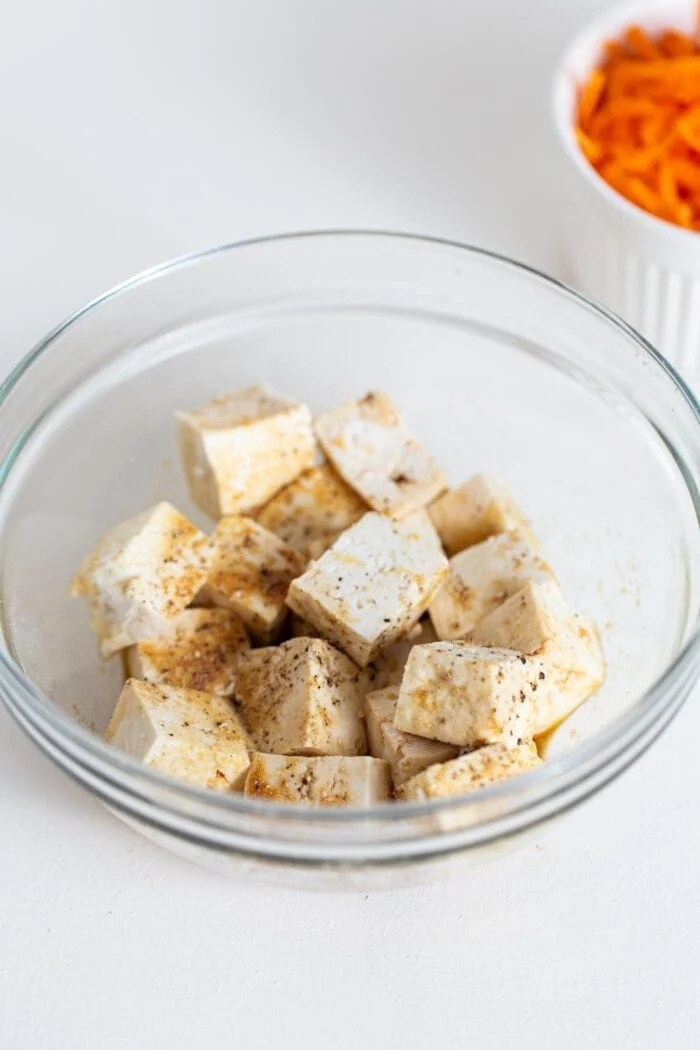 Cubed tofu in a bowl with soy sauce and pepper.