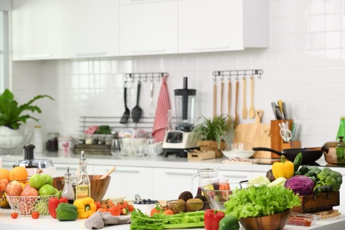 A kitchen with fruits and vegetables on the counter.