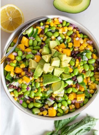 An overhead shot of a large bowl of salad with edamame, mango, cucumber and avocado.