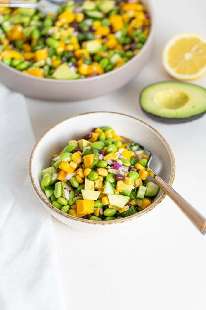 A bowl of edamame, cucumber, avocado and mango salad.