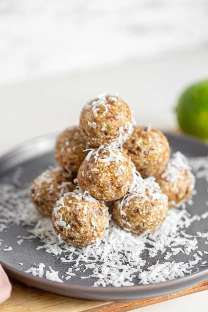 A stack of energy balls covered in shredded coconut on a plate.