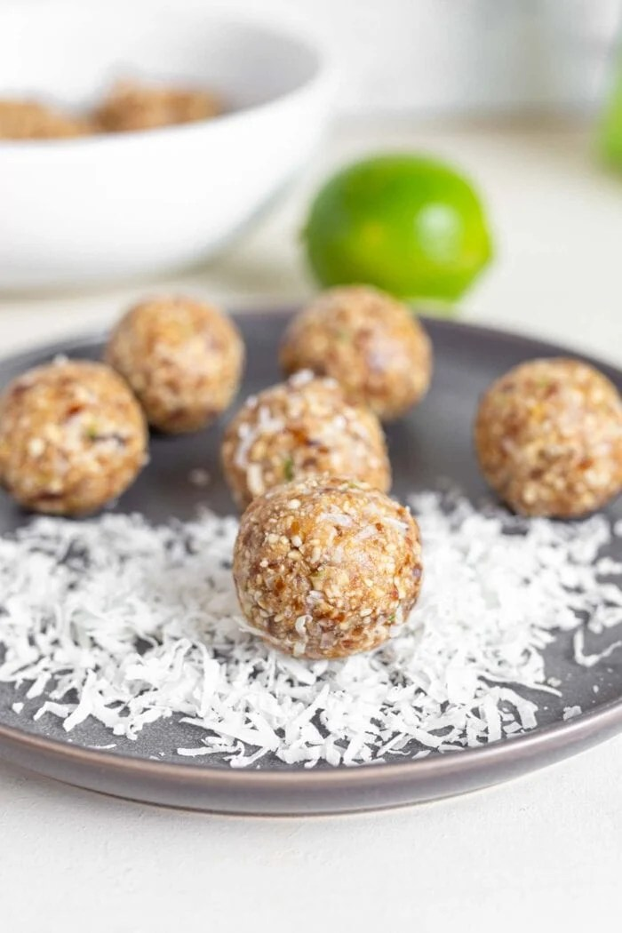 Raw energy balls and shredded coconut on a plate with a lime in the background.