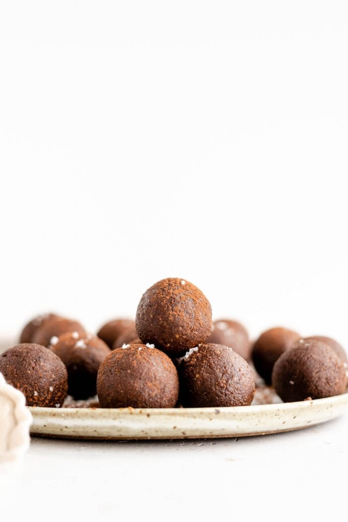 A stack of chocolate energy balls on a plate.