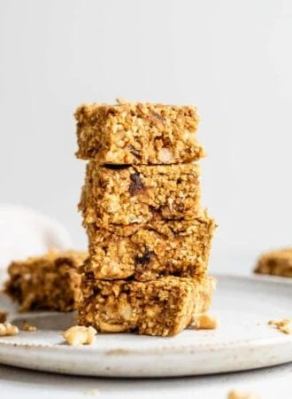 A stack of 4 pumpkin oat bars with dates and walnuts in them on a plate.