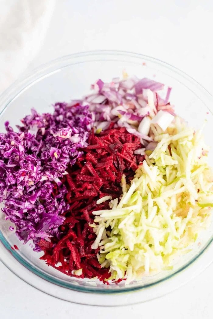 Shredded cabbage, beet, apple and red onion in a mixing bowl.