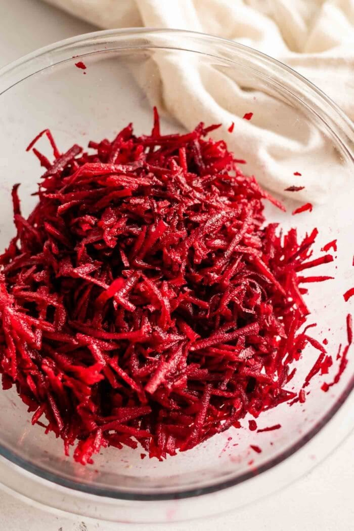 Raw grated beet in a glass mixing bowl.