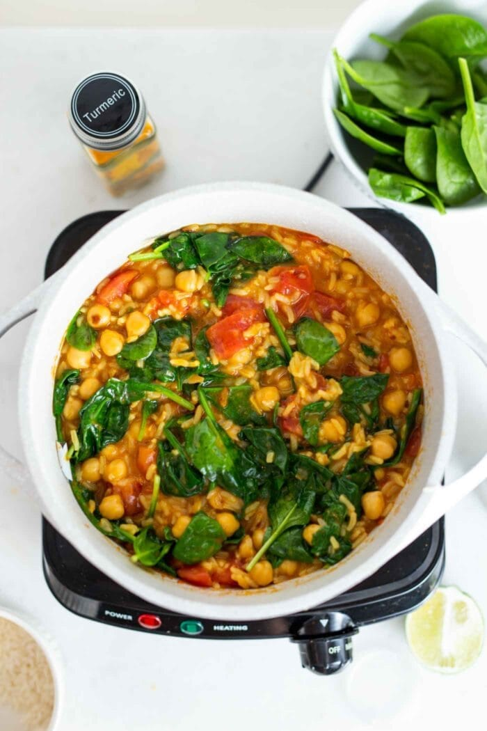 A pot of chickpea and rice stew with spinach.