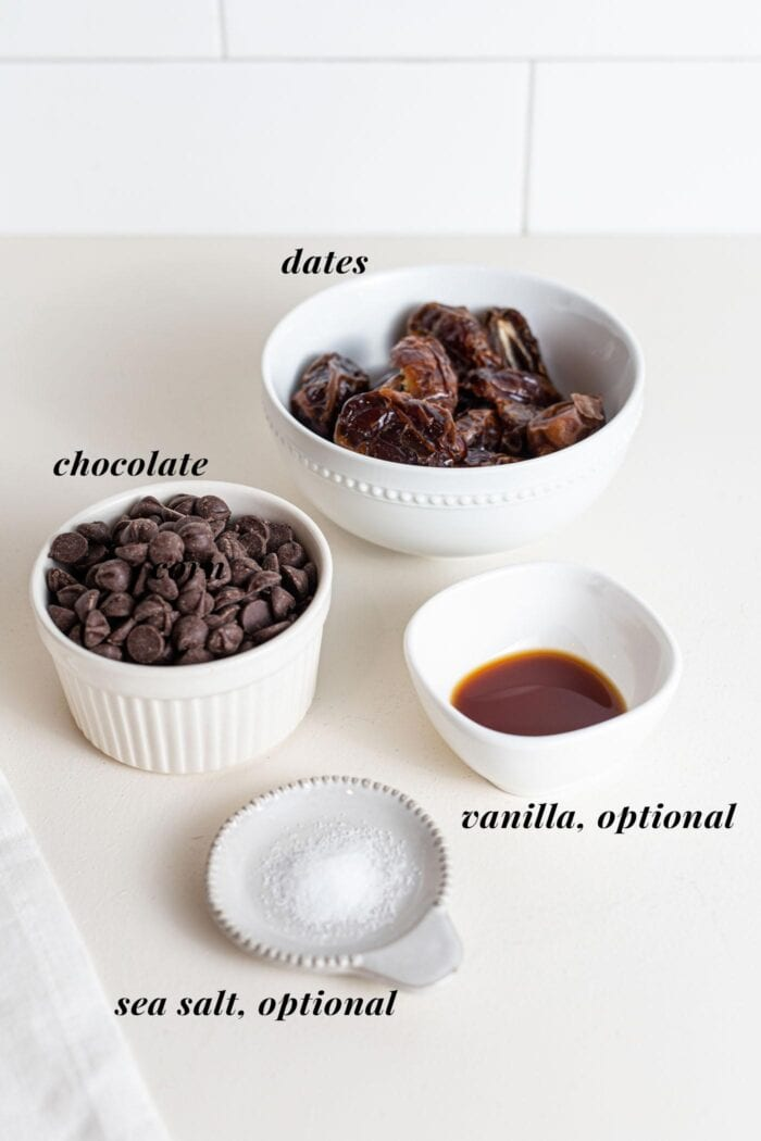 Chocolate, dates, vanilla and sea salt in small bowls on a counter.