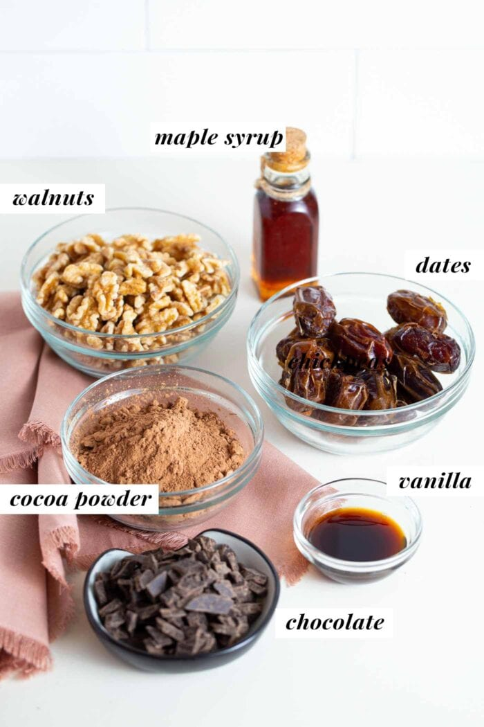 Chocolate, cocoa powder, walnuts, dates and vanilla in labelled containers.