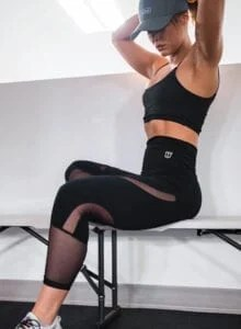 Fit woman sitting on a bench adjusting her hair.