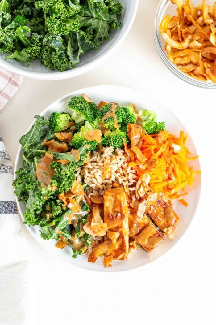 A bowl with tofu, sauce, kale, broccoli, carrot and coconut bacon.