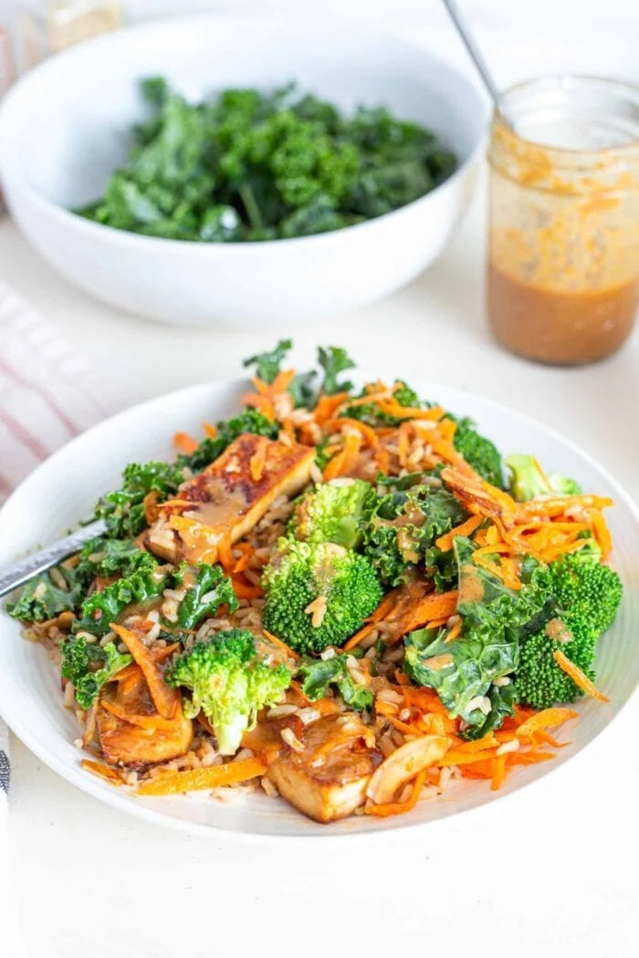 A bowl with shredded carrot, broccoli, tofu, kale and a creamy sauce.