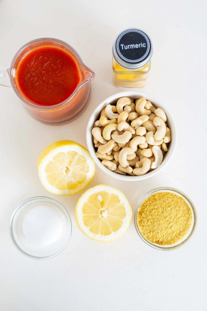 Cashews, nutritional yeast, lemon and tomato sauce in containers on a counter.