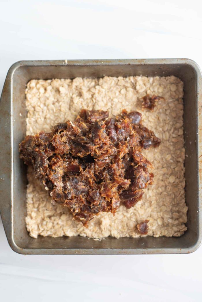 Date paste being spread over a crust in a baking pan.