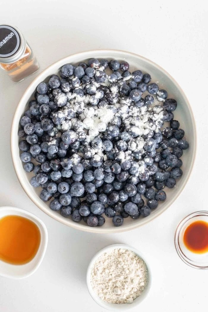 Fresh blueberries in a pie dish, sprinkled with cornstarch.