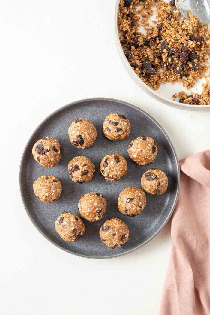 A number of no-bake cookie dough balls with raisins on a plate.