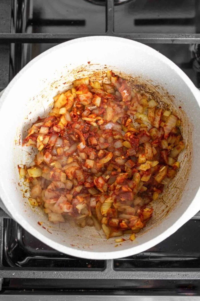 Onion, garlic, ginger and tomato paste cooking in a large soup pot on a gas range.