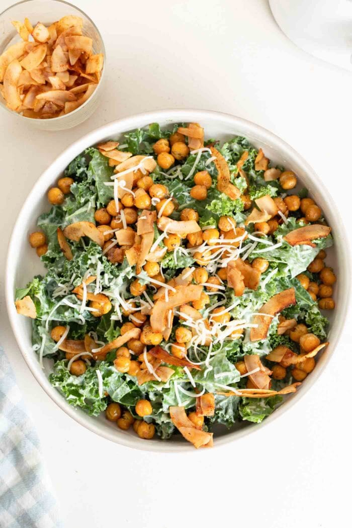 A large kale salad with dressing, chickpeas, parmesan and coconut bacon on top.