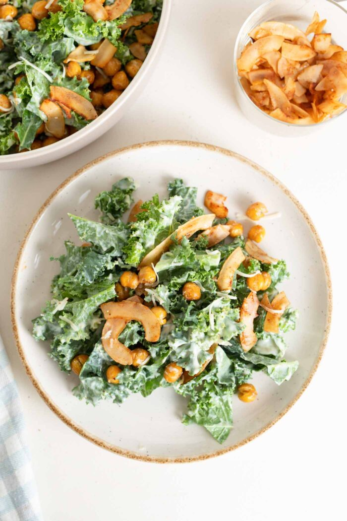 Overhead image of a kale caesar salad with chickpeas and coconut bacon on a plate.