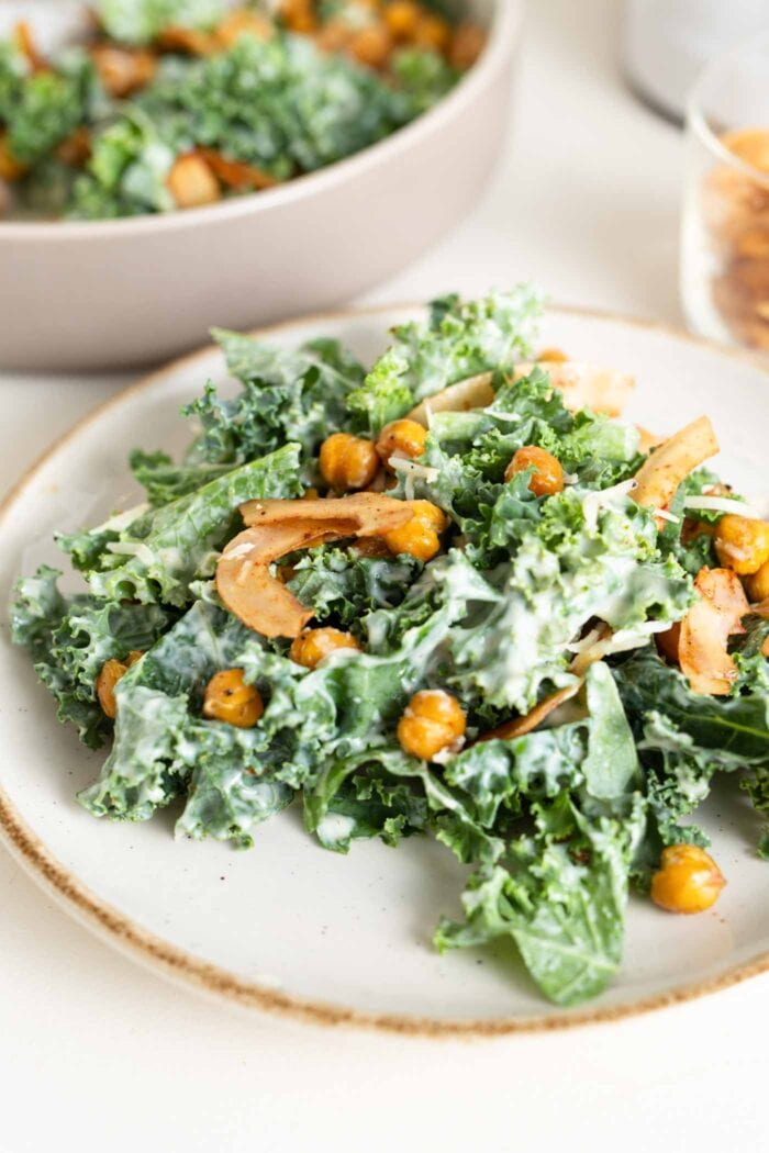 Close up of a kale salad on a plate with dressing, coconut bacon and chickpeas.