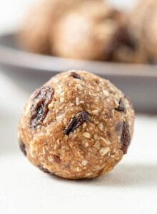 A close up of a cookie dough ball with raisins in it on a counter top.