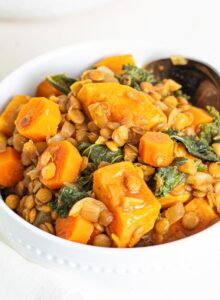 A bowl of sweet potato lentil stew with kale mixed into it.
