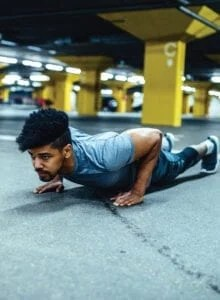 Fit man performing a push-up in a parking garage.