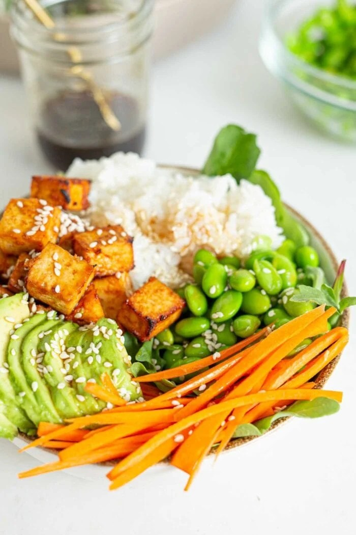Crisp baked tofu in a bowl with avocado, rice and edamame.