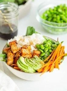 A bowl with tofu, avocado, carrot, edamame and rice.