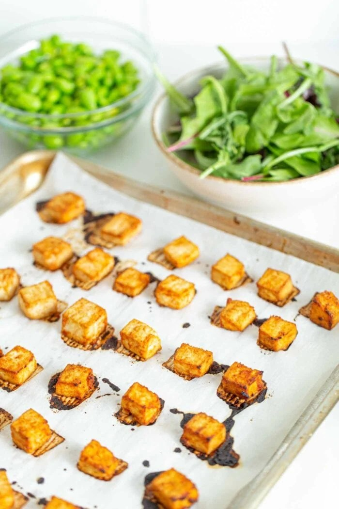 Baked tofu on a baking sheet with parchment paper.