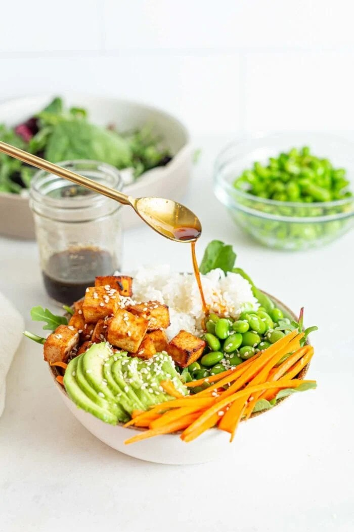 Drizzling a spoonful of sauce over a bowl of greens, avocado, carrot and tofu.