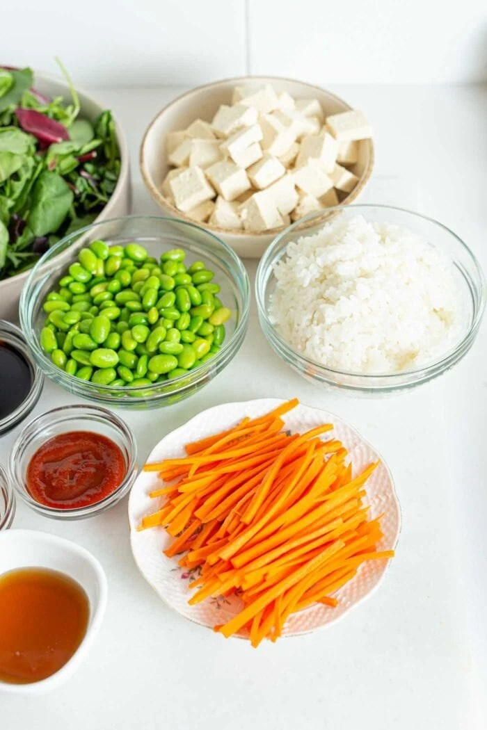 Sliced carrot, edamame, rice and tofu in bowls.