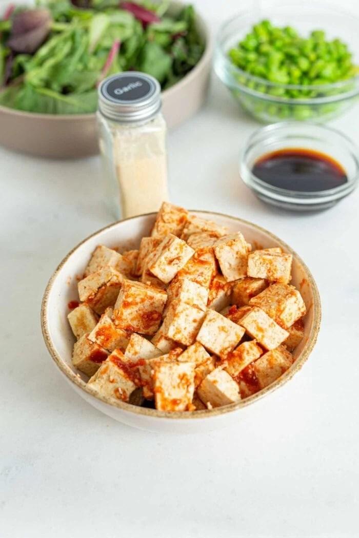 Cubed tofu in a bowl mixed with sriracha and garlic powder.