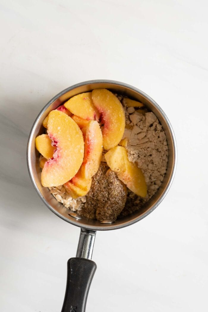 Sliced peaches, oats and flax in a saucepan.