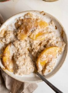 A bowl of peaches and cream oatmeal with a spoon in it.