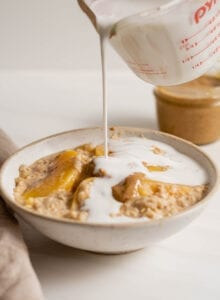 A measuring cup pouring milk into a bowl of peach oatmeal.