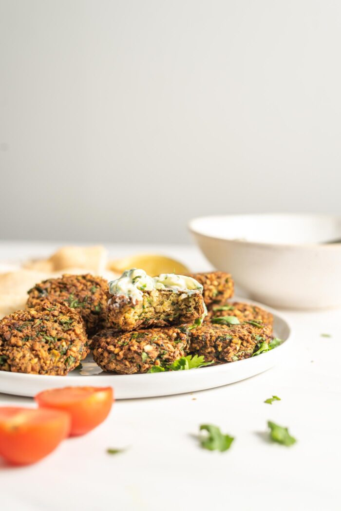 Crispy falafel patties on a plate, one is broken open and has tzatziki on top.