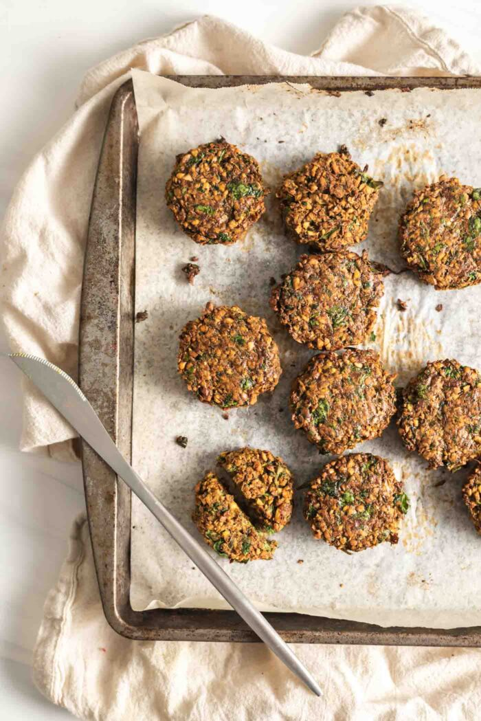 Crispy baked falafel on a baking tray lined with parchment paper.