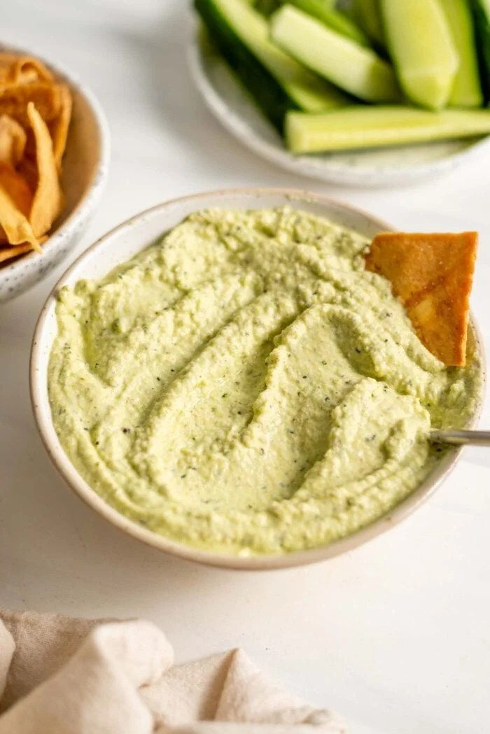 Bowl of green hummus with a spoon and pita chip in it.