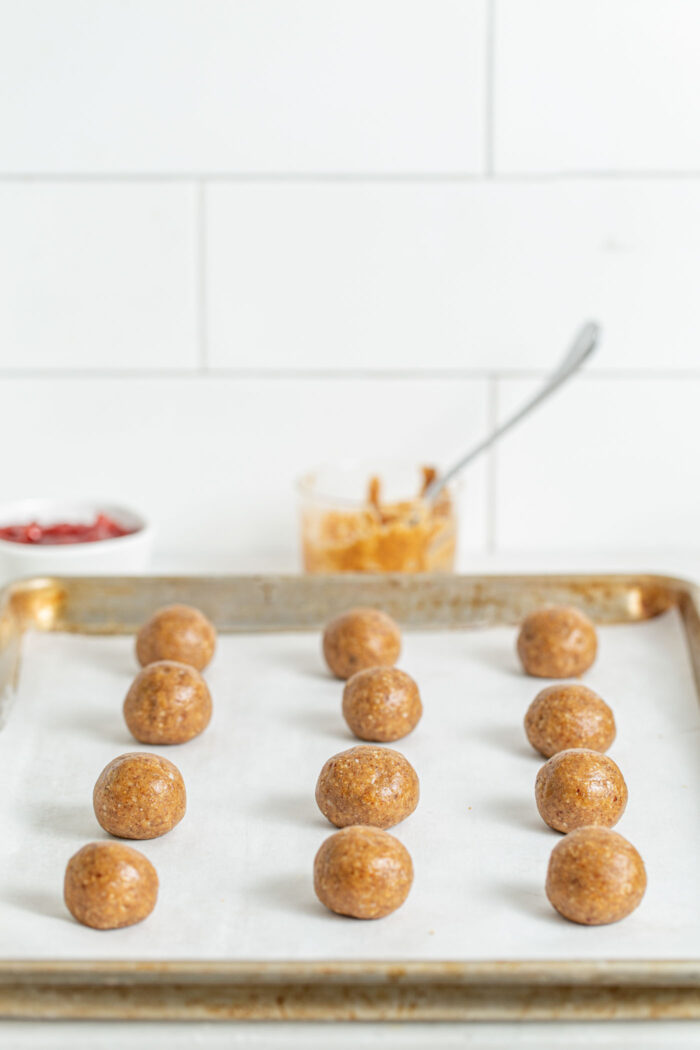 Balls of raw cooking dough on a baking sheet.