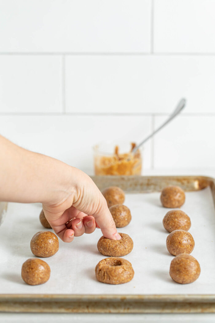 Pressing holes into cookie dough balls on a baking sheet.