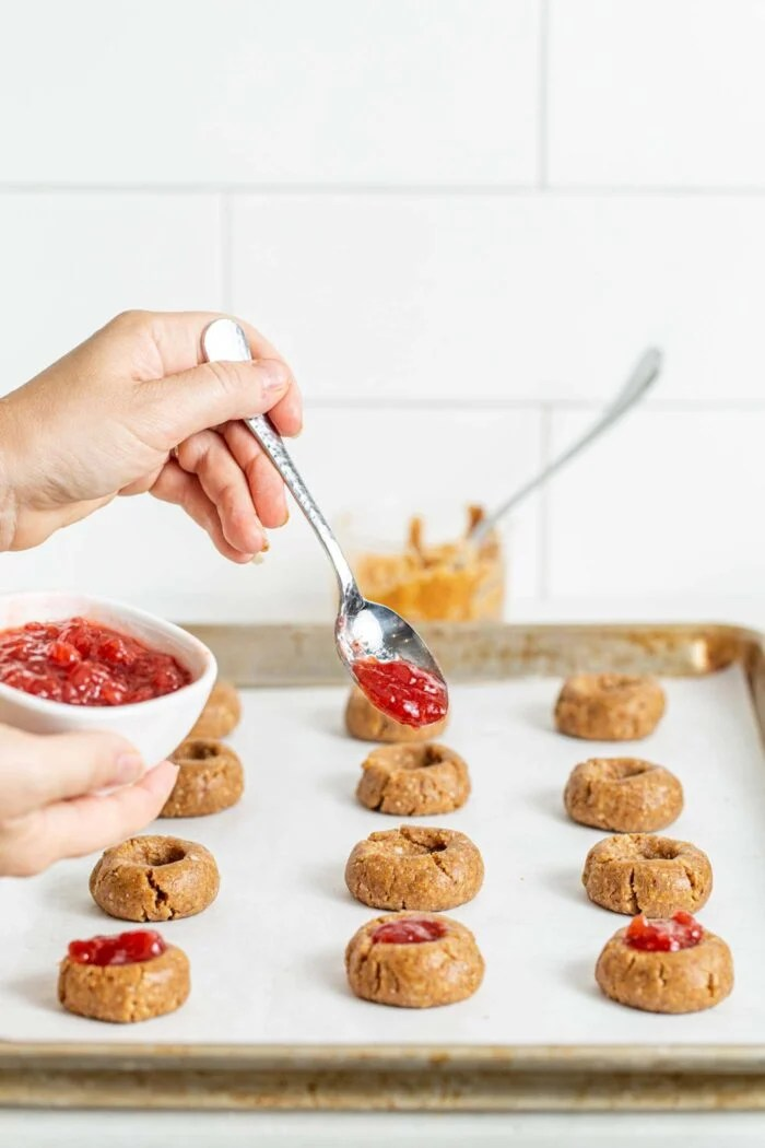 Spooning jam into thumbprint cookies on a baking tray.