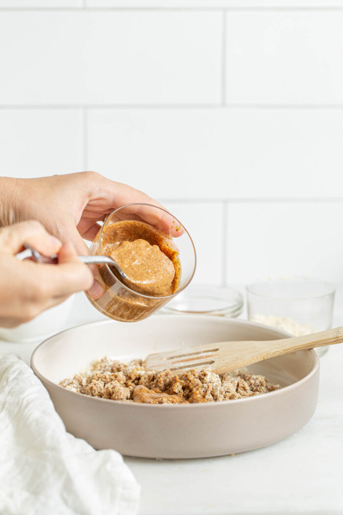 Scooping almond butter into a mixing bowl of cookie dough.