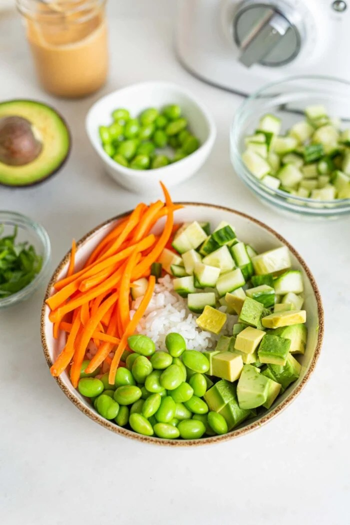 Rice, carrot, edamame and avocado in a bowl.
